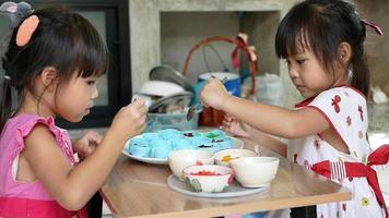de jolies filles de frères et sœurs ramassent de petits morceaux de gelée de pipo de différentes couleurs dans un moule pour préparer le dessert. les enfants préparent ensemble des desserts à la gelée dans la cuisine à la maison. video