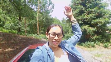 mulher alegre espalhou os braços no telhado do carro sob um céu brilhante na montanha com o fundo da natureza durante a viagem de férias. video