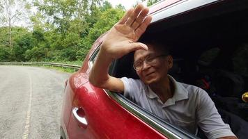 Happy senior man opens the window to see the beautiful view on the car enjoying a nature road trip with family. Smiling grandfather with head and hand out of car window enjoying view. video
