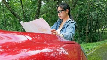 Woman traveling by car taking a break to look at a map while on a roadtrip in the national park. Female tourist leaning against a car front hood looking for directions on map. video