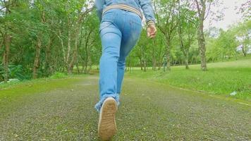 jambes en gros plan d'une touriste qui court sur la route avec une détente au milieu de la nature dans le jardin de printemps. concepts de voyage et de bonheur. video