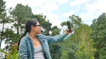 A happy female tourist talking video call on her smartphone with her friends on a summer vacation in a spring park. Travel and happiness concept.