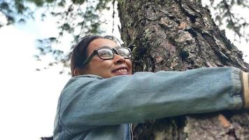 A happy woman is standing near majestic tree and hugs with love on a sunny summer day in the park. Earth day and non-deforestation concept. video