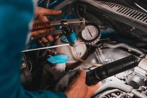 Professional car mechanic working in a car service, computer diagnostics of the bonnet space in the car. photo
