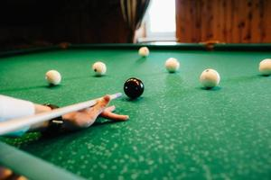 elegant young man in a dark suit plays billiards photo