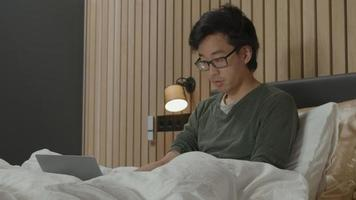 Man in bed watches laptop video