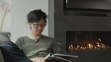 Man sits in living room and reads a magazine video
