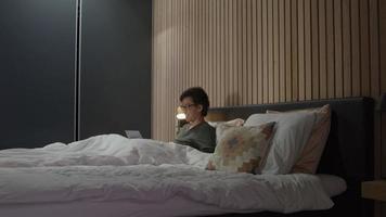 homme au lit ayant une conversation en ligne sur un ordinateur portable video
