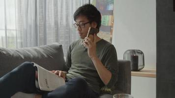 Man in living room reads and answers call on mobile phone video