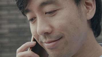 un homme debout à l'extérieur termine l'appel sur son smartphone et respire profondément video