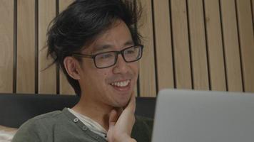 Man in bed having vivid online conversation on laptop video