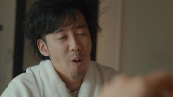 Man in bathrobe sitting at breakfast table talking to woman video