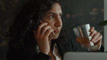 une femme est assise avec un ordinateur portable tout en appelant et en buvant video