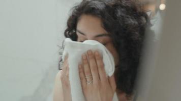 donna in bagno si guarda allo specchio asciugandosi il viso e sistemandosi i capelli video