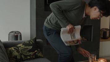l'homme s'assied dans le salon et lit un magazine video