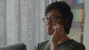 Man in living room calls with mobile phone video