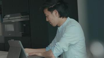 l'uomo in cucina con il laptop alza lo sguardo e fa spallucce video
