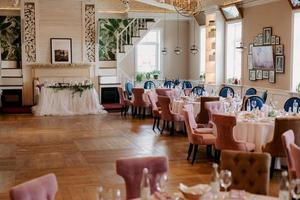 the presidium of the newlyweds in the banquet hall of the restaurant is decorated with candles and green plants photo