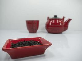 té chino y una tetera roja con una taza en el bachground foto
