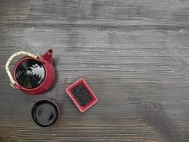 Juego de té rojo sobre una mesa de madera. tetera roja, taza y té chino. vista superior con espacio de copia foto
