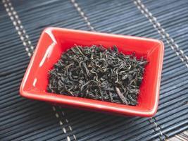 té chino en plato rojo pequeño. de cerca foto
