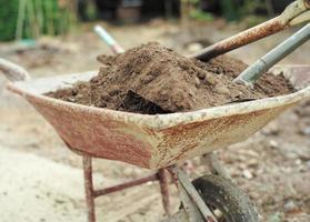 Closeup pile of soil on the steel shovels in the wheelbarrow photo