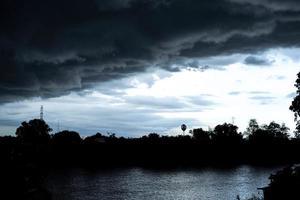 silueta de paisaje de árboles y torre eléctrica con nube de lluvia en el cielo brillante que se refleja en la superficie del río foto