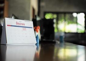 Calendario de primer plano sobre la mesa con luz bokeh borrosa de fondo. concepto de trabajo desde el hogar. palabra tailandesa en el calendario significa junio en inglés foto