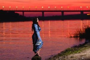 Hermosa joven con largo cabello ondulado oscuro de pie en la orilla del río foto