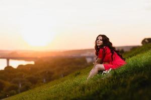 Hermosa joven sentada en una pendiente cubierta de pasto verde foto