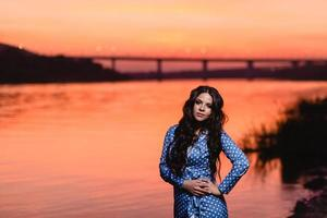 Beautiful young girl with long dark wavy hair standing at the bank of the river photo