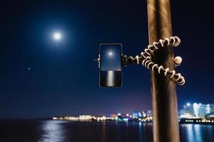 Using a smartphone on a foldable tripod with long exposure of the sea at night photo