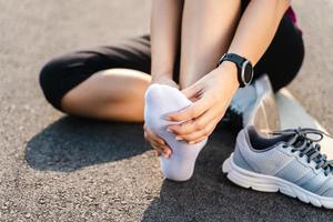 Running injury leg accident- sport woman runner hurting holding painful sprained ankle in pain. Female athlete with joint or muscle soreness and problem feeling ache in her lower body. photo
