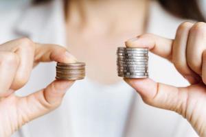 las manos comparan dos pilas de monedas de diferentes tamaños. foto