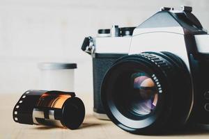 Antigua cámara de película slr de 35 mm y un rollo de película sobre fondo de madera. concepto de fotografía flim. foto