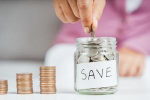 Mano de mujer poniendo moneda de dinero en frasco de vidrio para ahorrar dinero. Ahorro de dinero y concepto financiero. foto