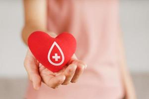 Woman hands holding red heart with blood donor sign. healthcare, medicine and blood donation concept photo