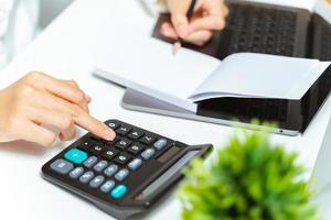 Close up of woman hand using calculator and writing a note in home or office. photo