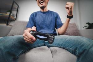 emocionado joven guapo jugando videojuegos y levantando los puños sentado en el sofá en casa. foto