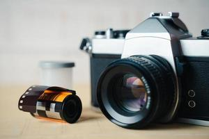 Old SLR film camera and a roll of film on wooden background. photo