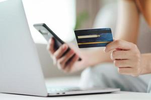 Young woman holding credit card and using smart phone for online shopping, internet banking, e-commerce, spending money, working from home concept photo