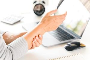 Closeup woman holding her wrist pain from using computer long time. Office syndrome concept. photo