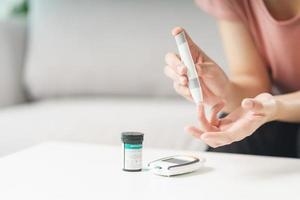 Mujer asiática con lanceta en el dedo para controlar el nivel de azúcar en la sangre con un medidor de glucosa, atención médica y médica, diabetes, concepto de glucemia foto