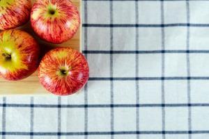 manzanas rojas frescas sobre tabla de cortar de madera y fondo de toalla. foto