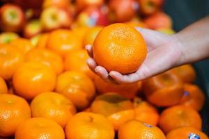 Mano de mujer eligiendo una naranja en el supermercado foto