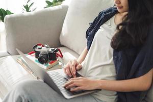 Fotógrafo de mujer asiática sentado en el sofá usando la computadora portátil para trabajar con cámara de película slr en casa, concepto creativo, empleado independiente. foto