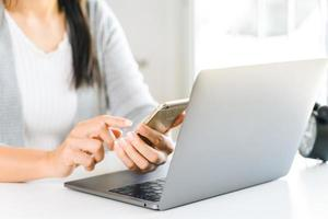 young woman using mobile phone with laptop computer. photo