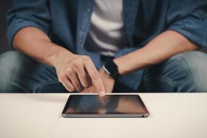 cerca de joven con tableta en el sofá. búsqueda, navegación, compras en línea, redes sociales. foto