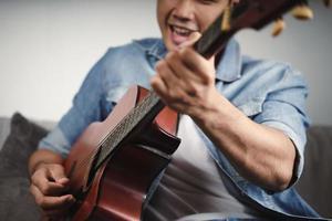 Disfrute de un apuesto hombre asiático practicando o tocando la guitarra en el sofá de la sala de estar foto