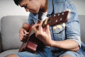 Enjoy handsome asian man practicing or playing the guitar on the sofa at living room photo